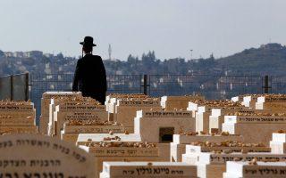 Ορθόδοξος Εβραίος προσεύχεται σε τάφο του Χαρ Χαμενουτσότ, με θέα την Ιερή Πόλη.
