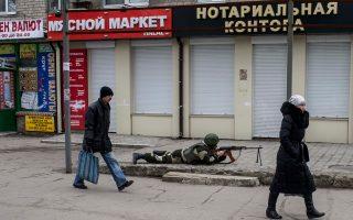 Κάτοικοι του Ντονέτσκ περνούν έξω από κλειστά μαγαζιά, δίπλα στον στρατιώτη που σκοπεύει με το όπλο του. Στη διάρκεια του χειμώνα, πολλοί άνθρωποι πέθαναν κυριολεκτικά από πείνα.
