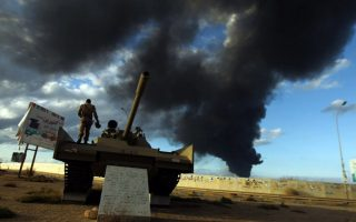 A member of the Libyan army stands on a tank as heavy black smoke rises from the city's port in the background after a fire broke out at a car tyre disposal plant during clashes against Islamist gunmen in the eastern Libyan city of Benghazi on December 23, 2014. Forces loyal to former general Khalifa Haftar and to internationally recognised Prime Minister Abdullah al-Thani have been battling for weeks against Islamists who have taken control of much of Libya's second city, and the capital Tripoli. AFP PHOTO / ABDULLAH DOMAABDULLAH DOMA/AFP/Getty Images