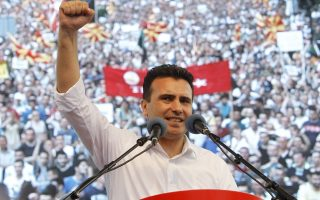 Zoran Zaev, the leader of the opposition social democrats, rises his fist during his speech on a protest in front of the Government building in Skopje, Macedonia, on Sunday, May 17, 2015. Macedonian opposition started massive demonstrations Sunday in Skopje protesting against the conservative government of the Prime Minister Nikola Gruevski, demanding its resignation. (AP Photo/Boris Grdanoski)