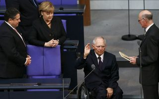 German Economy Minister Sigmar Gabriel and Chancellor Angela Merkel watch as Finance Minister Wolfgang Schaeuble is sworn-in by Parliament President Norbert Lammert (L-R) during the meeting of Germany's lower house of parliament, Bundestag in Berlin December 17, 2013.    REUTERS/Tobias Schwarz (GERMANY  - Tags: POLITICS)