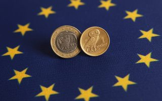 An one Euro (L) and one Greek Drachma coins are displayed on an European flag in this picture illustration taken in Istanbul June 14, 2012. On Sunday, Greece votes in an election where a radical left party that opposes the strict terms of the country's bailout could emerge victorious, increasing the chances of it abandoning the euro and returning to the drachma. REUTERS/Murad Sezer (TURKEY - Tags: POLITICS BUSINESS)
