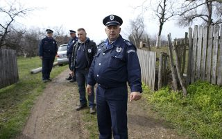 A group of police officers stands in the village of Velika Ivanca, about 40 km (25 miles) southwest of Belgrade April 9, 2013. A gunman shot dead 13 people, including his mother and son, in an early-morning rampage through a small Serbian village southwest of the capital Belgrade on Tuesday, authorities said. Those killed included a two-year-old child. The gunman, identified by police as Ljubisa Bogdanovic - a war veteran born in 1953 - also shot his wife before turning the gun on himself. Both were in critical condition in hospital, police said.      REUTERS/Marko Djurica (SERBIA  - Tags: CRIME LAW)