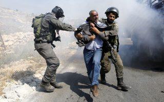 Ισραηλινός αστυνομικός συλλαμβάνει Παλαιστίνιο, ενόσω κατεδαφίζεται το σπίτι του στη Χεβρώνα.