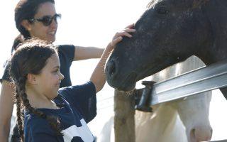 Eνα κοριτσάκι και η μαμά του χαϊδεύουν άλογα στο Κλίβελαντ των ΗΠΑ.