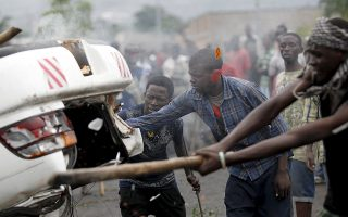 Protesters destroy a car belonging to a policeman after they intercepted him at a barricade during demonstrations against the ruling CNDD-FDD party's decision to allow President Pierre Nkurunziza to run for a third five-year term in office, in Bujumbura, Burundi April 30, 2015. A senior U.S. diplomat told Burundi's President, Pierre Nkurunziza, on Thursday that the east African country risks boiling over if it stifles political opposition, as protests against the president entered a fifth day. Tom Malinowski, U.S. assistant secretary of state for democracy, human rights and labor, arrived in Burundi on Wednesday to try to help halt escalating unrest and defuse the country's biggest crisis in years, set off by Nkurunziza's decision to seek a third term in office.  REUTERS/Thomas Mukoya      TPX IMAGES OF THE DAY