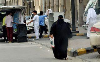 Γυναίκα, που φοράει την απαιτούμενη μπούργκα, περπατά στους δρόμους του Ριάντ.