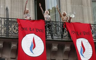 Three topless activists from the Ukrainian feminist group Femen stand on a balcony behind banners which read,