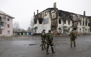 A  pro-Russian rebels walk past a destroyed building in the town of Vuhlehirsk, Ukraine, Friday, Feb. 6, 2015. German Chancellor Angela Merkel and French President Francois Holland are set to hold talks with Russian President Vladimir Putin in the Kremlin on Friday, one day after discussing peace proposals for Ukraine's conflict with Ukrainian President Petro Poroshenko. (AP Photo/Petr David Josek)