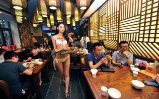 Να σου κόβεται η όρεξη. Έξυπνος ο επιχειρηματίας του εικονιζόμενου εστιατορίου στην Κίνα. Προσέλαβε μοντέλα, αγόρια και κορίτσια, για να σερβίρουν με τα μαγιό τους, γνωρίζοντας ότι έτσι θα μάζευε κόσμο που θα ήθελε να φάει και να «δει». Δεν σκέφτηκε όμως τις γυναίκες πελάτισσες. Που μόλις θα έρθει η σερβιτόρα με το μπικίνι, εκείνες αυτομάτως θα ξεκινήσουν αυστηρή δίαιτα. AFP PHOTO