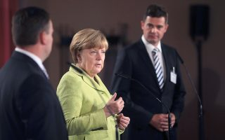 German chancellor Angela Merkel attends a press conference next to chairman of CDU Thuringia Mike Mohring (R) and chairman of CDU Saxony-Anhalt Andre Schroeder of the Christian Union CDU/CSU faction conference in Magdeburg, eastern Germany, on June 22, 2015. AFP PHOTO / DPA / JENS WOLF GERMANY OUT
