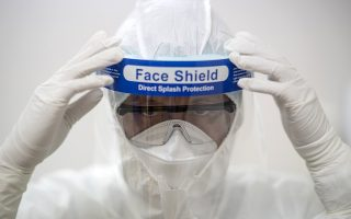 A member of medical personnel put on a face shield during a drill as part of preparations in the event of a Middle East Respiratory Syndrome (MERS) outbreak, at a private hospital in Bangkok, Thailand, June 24, 2015. Thailand, which reported its first case of MERS last week, on Monday said it had no new cases, raising hopes the virus there had been contained. REUTERS/Athit Perawongmetha