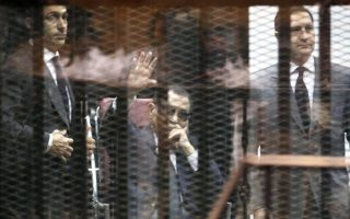 epa04782340 (FILE) A file photo dated 09 May 2015 shows former Egyptian President, Hosni Mubarak (C), flanked by his sons Gamal Mubarak (L) and Alaa Mubarak (R), waving from the defendants' cage during their trial at the Police Academy in Cairo, Egypt. Egypt's highest appeals court on 04 June ordered a retrial for former president Mubarak on charges relating to the deaths of protesters, after granting an appeal by the prosecution. The Court of Cassation set November 5 for the start of the retrial of Mubarak, former interior minister Habib al-Adly and six former police chiefs in the same case.  EPA/KHALED ELFIQI