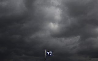 A Greek flag flutters atop the Acropolis hill in Athens, Greece in this February 18, 2015 file photo. Euro zone leaders are expected to gather for an emergency summit this week to try to avert a Greek default.  REUTERS/Yannis Behrakis/FilesGLOBAL BUSINESS WEEK AHEAD PACKAGE - SEARCH