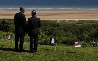 U.S. President Barack Obama, left,  and French President Francois Hollande look out at Omaha Beach, one of the sites of the Allied soldiers beach landings, at Normandy American Cemetery as they participate in the 70th anniversary of D-Day, in Colleville sur Mer, Normandy, France, Friday, June 6, 2014. (AP Photo/Charles Dharapak)
