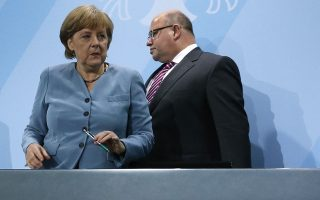 German Environment Minister Peter Altmaier (R) and Chancellor Angela Merke arrive to address a news conference after an energy