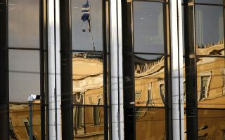 The Greek parliament is reflected on the Foreign Ministry building in Athens March 12, 2015. Greece has promised its lenders to reform its state sector, to implement labour reforms, such as opening up closed professions, to make its economy more competitive, improve its tax administration and fight tax evasion and corruption, which have been widely blamed for the debt crisis. REUTERS/Yannis Behrakis (GREECE - Tags: POLITICS BUSINESS)