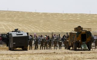 Turkish soldiers stand guard as Syrian refugees wait behind the border fences to cross into Turkey on the Turkish-Syrian border, near the southeastern town of Akcakale in Sanliurfa province, Turkey, June 5, 2015. More than 3,000 Syrians fleeing clashes between Islamic State and Kurdish fighters have crossed into Turkey since Wednesday, a Turkish government official said. Kurdish forces are trying to drive the militants out of Tel Abyad, in Syria's Hassakah province, close to the Turkish border town of Akcakale. The official said 3,337 Arab Syrians had crossed into Turkey in less than two days to avoid the clashes and bombing raids carried out against IS by a U.S.-led coalition. REUTERS/Osman Orsal