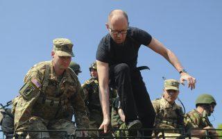 Ο Ουκρανός πρωθυπουργός Αρσένι Γιάτσενιουκ αποβιβάζεται από τεθωρακισμένο όχημα μεταφοράς προσωπικού στο Διεθνές Κέντρο Ειρηνευτικών Αποστολών και Ασφαλείας, στο Λβοφ της δυτικής Ουκρανίας.