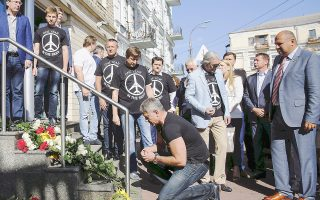 Φορώντας μπλουζάκια που γράφουν «ένα χρόνο στον ουρανό», Ουκρανοί πολίτες αφήνουν λουλούδια στη μνήμη όσων χάθηκαν στην πτήση ΜΗ17 μπροστά από την ολλανδική πρεσβεία του Κιέβου.