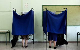 People place their votes inside of voting booths during the Greek referendum, to decide whether or not Greece will accept the bailout conditions proposed jointly by the European Commission, the International Monetary Fund and the European Central Bank, on July 5, 2015 in Athens. Prime Minister Alexis Tsipras said the referendum will determine its