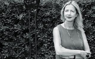 Η Iwona Blazwick φωτογραφημένη στον κήπο της Γαλλικής Σχολής μπροστά από έργο της Caroline Achaintre.
