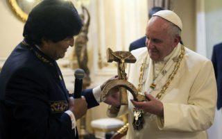 Ο Εσταυρωμένος του σφυροδρέπανου. Με χαρά δέχθηκε το δώρο του ο Πάπας Φραγκίσκος από τον Πρόεδρο της Βολιβίας,  Evo Morales κατά την διάρκεια επίσκεψής του στην Λατινική Αμερική. Λίγο πριν είχε την δυνατότητα να παρατηρήσει και τα τοπικά προϊόντα της χώρας όπως πατάτες και φύλλα κόκας.  (L'Osservatore Romano/Pool Photo via AP)