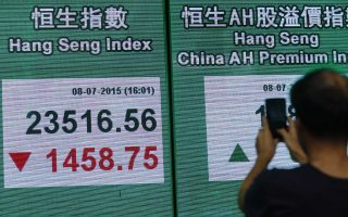 A man takes a photograph of an electronic board showing the Hang Seng Index in Hong Kong on July 8, 2015. Hong Kong equities plunged almost six percent July 8, to a seven-month low as a rout in China spread into regional markets with traders also buffeted by fears for Greece's future in the eurozone. AFP PHOTO / ISAAC LAWRENCE