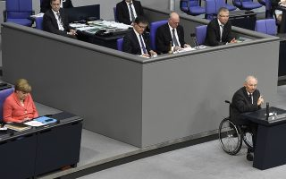 German Chancellor Angela Merkel (L) listens as German Finance Minister Wolfgang Schaeuble (R) gives a speech during a special session at the Bundestag (lower house of parliament) in Berlin on July 17, 2015. German lawmakers rally to vote on a new Greece bail-out deal, two days after the parliament in Athens grudgingly agreed to harsh reforms. AFP PHOTO / TOBIAS SCHWARZ