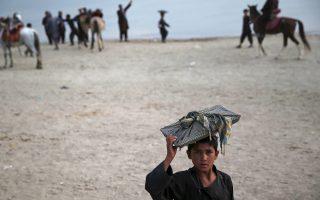Ενα παιδί από το Αφγανιστάν κουβαλάει ψωμί προς πώληση στο κεφάλι του, κατά μήκος της λίμνης Κάργκα στην Καμπούλ.