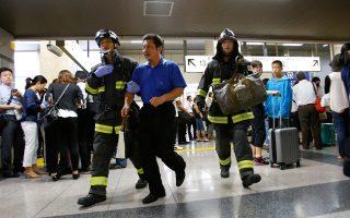 Πυροσβέστες βοηθούν έναν επιβάτη να αποβιβαστεί από το γεμάτο καπνό βαγόνι της υπερταχείας. Τρία άτομα διακομίστηκαν σε σοβαρή κατάσταση σε νοσοκομεία της περιοχής εξαιτίας της εισπνοής καπνού.