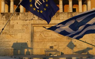 Pro-Euro demonstrators wave a Greek flag, right, and a European Union flag in front of the Tomb of the Unknown Soldier monument during a rally in Syntagma Square in Athens, in this photo dated Thursday, July 9, 2015. The latest incarnation of Greece's economic crisis over the span of a month saw Greece in the end accept harsh austerity measures from creditors to save the country from bankruptcy and possibly ignominiously getting kicked out of the eurozone. (AP Photo/Petros Karadjias)