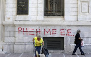 A municipality worker clears the sidewalk outside a bank as the graffiti reading ''Rupture with EU'' in Athens, Monday, July 6, 2015. Greek Finance Minister Yanis Varoufakis resigned Monday, saying he was told shortly after Greece's decisive referendum result that some other eurozone finance ministers and the country's other creditors would appreciate his not attending the ministers' meetings. (AP Photo/Petr David Josek)