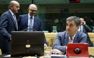 Greek Finance Minister Euclid Tsakalotos (R) waits for the start of a euro zone finance ministers meeting next to Spain's Economy Minister Luis de Guindos (L) and European Economic and Financial Affairs Commissioner Pierre Moscovici in Brussels, Belgium, July 12, 2015. Euro zone leaders will fight to the finish to keep near-bankrupt Greece in the euro zone on Sunday after the European Union's chairman cancelled a planned summit of all 28 EU leaders that would have been needed in case of a