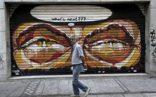 epa04800110 A man walks in front of a closed shop shutter covered with graffiti in central Athens, Greece, 15 June 2015. European Commission President Jean-Claude Juncker broke off high-level bailout talks with Greek officials on 14 June, after weekend negotiations failed to deliver progress on 'significant gaps' in reform plans for the cash-strapped country.  EPA/YANNIS KOLESIDIS
