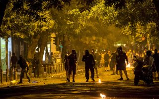 Masked youth walk along a street during minor clashes in central Athens, Greece late July 5, 2015. Greeks voted overwhelmingly