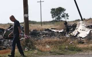 A Malaysian air crash investigator works at a crash site of the Malaysia Airlines Flight MH17 near the village of Hrabove (Grabovo), Donetsk region July 24, 2014. REUTERS/Maxim Zmeyev (UKRAINE - Tags: TRANSPORT DISASTER)