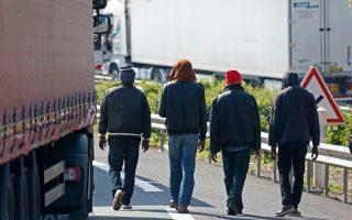 Μετανάστες περπατούν πλάι στα σταθμευμένα φορτηγά, αναζητώντας κάποιο τρόπο να διεισδύσουν στο εσωτερικό τους για να περάσουν στη Βρετανία.