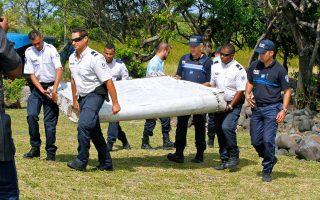 Γάλλοι αστυνομικοί μεταφέρουν τμήμα φτερού από τα συντρίμμια αεροπλάνου που εντοπίσθηκαν στο Σεν Αντρέ της νήσου Ρεϊνιόν.