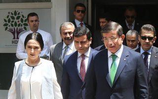 Ο Αχμέτ Νταβούτογλου  (δεξιά) με τους συμπροέδρους του φιλοκουρδικού κόμματος HDP, μετά τη χθεσινή τους συνάντηση.