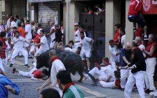 Συμμετέχοντες στη γιορτή της Παμπλόνα τρέχουν μπροστά από ταύρο στα στενά δρομάκια της πόλης.