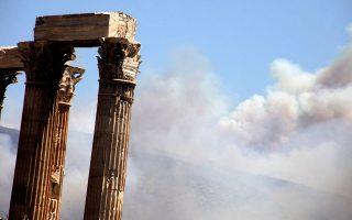 Ο καπνός από την πυρκαγιά στον Υμηττό έπνιξε την Αθήνα, οι στύλοι του Ολυμπίου Διός σκιάστηκαν.