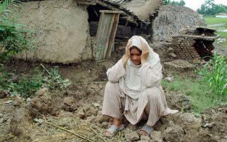 Μία γυναίκα κάθεται έξω από το κατεστραμμένο από την καταρρακτώδη βροχή σπίτι της.