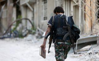 Μαχητής του Ελεύθερου Συριακού Στρατού βαδίζει σε προάστιο της Δαμασκού με το Κοράνι ανά χείρας.