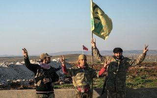 Μέλος κουρδικής πολιτοφυλακής στην επαρχία Χαλεπίου σχηματίζει το σήμα της νίκης, με φόντο πορτρέτο του φυλακισμένου ηγέτη του ΡΚΚ Αμπντουλάχ Οτσαλάν και τεθωρακισμένο των τουρκικών ενόπλων δυνάμεων.