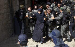 Ισραηλινοί συνοριακοί φρουροί απωθούν Παλαιστίνιες γυναίκες στην παλιά πόλη της Ιερουσαλήμ.