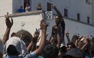 Pakistani migrants shout as they want to be registered at a police station at the southeastern island of Kos, Greece, Wednesday, Aug. 19, 2015. More than 130,000 migrants have reached Greece so far in 2015, according to official estimates, straining the country's resources. (AP Photo/Alexander Zemlianichenko)