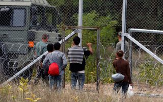 Πρόσφυγες στα σερβοουγγρικά σύνορα περνούν από τα σημεία στα οποία δεν έχει ολοκληρωθεί η ανέγερση του φράκτη.