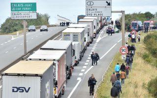 Αστυνομικοί εμποδίζουν πρόσφυγες να προσεγγίσουν φορτηγά στο λιμάνι του Καλαί.