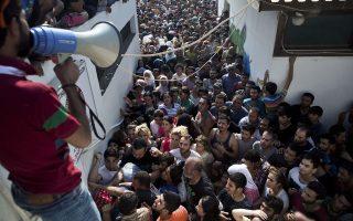 Πρόσφυγες συνωστίζονται έξω από το στάδιο της Κω όπου λαμβάνει χώρα η διαδικασία καταγραφής τους.
